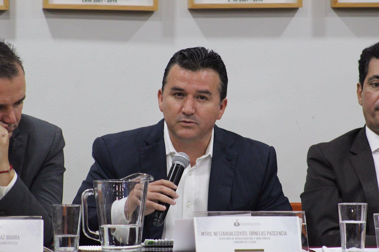 Foto del secretario hablando en un congreso con otros funcionarios.