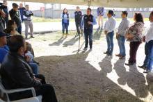 Foto de varios funcionarios de pie y sentados inaugurando una obra vial.