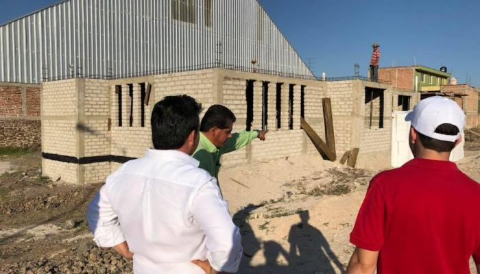 Foto del secretario con otras personas revisando una de las obras del programa Vamos juntos.