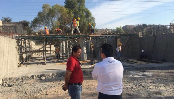 Foto del secretario con una persona revisando una construcción.