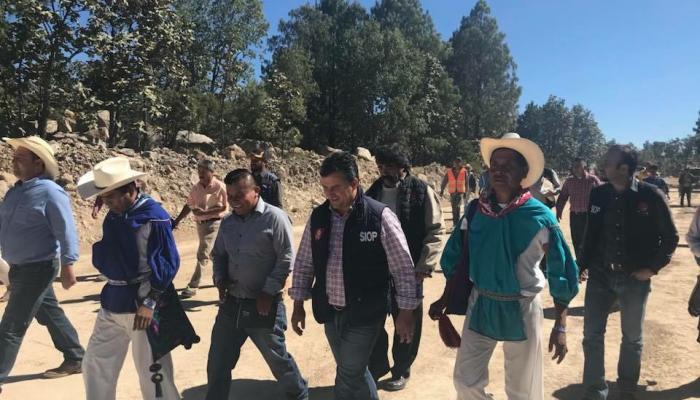 Foto del secretario con personas de la comunidad wixárika revisando una construcción.